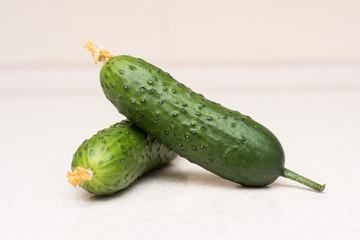 Couple of ripe green cucumbers with a tassel and flower on the kitchen table