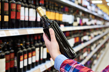 Woman with bottle of wine in store