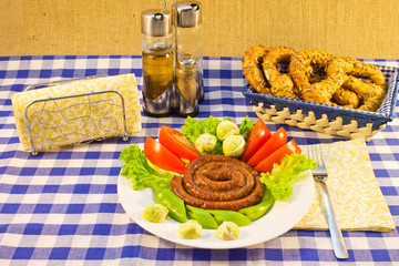 Sausages fried twisted into the spiral with vegetables