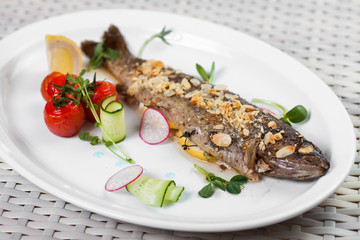 baked fish with a lemon and vegetables on a white dish
