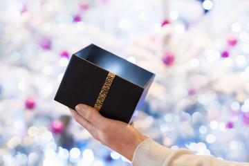 Woman opens a black box gift in front of a Christmas tree