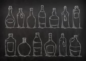 Set of cartoon doodle bottles. Sketch glass bottles for food design, menu. Decorative vector illustration isolated on chalkboard. All bottles are grouped for easy editing.