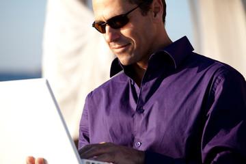 homme d'affaire sur son ordinateur avec des lunettes de soleil