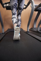 Female legs on a treadmill.