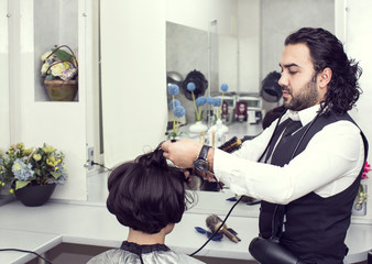 Hairdresser makes hair woman in a beauty salon