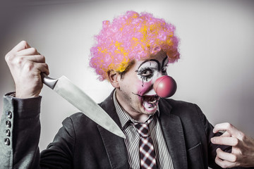 scary clown with a knife in his hand