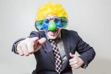 the clown shows his fingers in front of dressed as a businessman