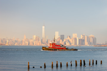 Wall Mural - Tugboat in New York Harbor in afternoon soft winter light with the Financial District of Lower Manhattan in background. New York City