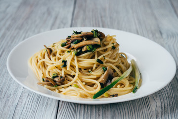 Spaghetti with mushrooms and onions on a white plate