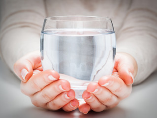 A glass of clean mineral water in woman's hands. Environment protection, healthy drink.