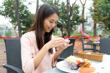 Woman taking photo on food in outdoor restaurant