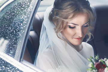 Beautiful blonde bride posing in wedding car on rainy day
