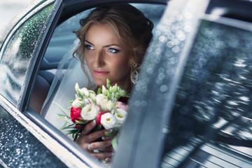 Beautiful blonde bride posing in wedding car on rainy day