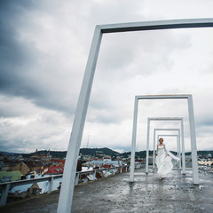 Gorgeous blonde bride posing on roof under clouds