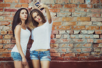 girlfriends taking a selfie in urban city context. Concept of friendship and fun with new trends and technology. Best friends eternalizing the moment with modern smartphone