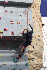 Active boy climbing an outdoor wall upto the top