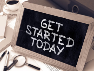 Get Started Today Handwritten by White Chalk on a Blackboard. Composition with Small Chalkboard on Background of Working Table with Office Folders, Stationery, Reports. Blurred, Toned 3d Image.