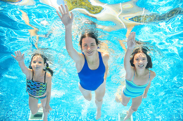 Family swims in pool or sea under water, happy active mother and children have fun underwater, kids sport on family vacation