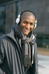 Young Black Man Listening to Music in the Street with White Earphones