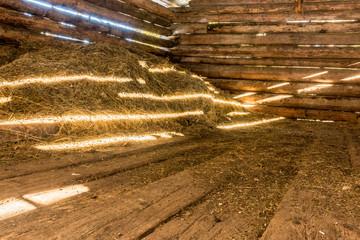 Heuhaufen in einem Holzstadel beleuchtet von Sonnenstrahlen