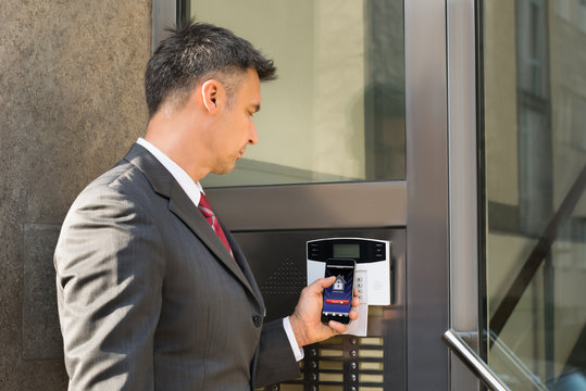 Businessman Disarming Security System Of Door With Smartphone
