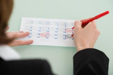 Fototapete - Businesswoman Hand Setting Important Date On Calendar