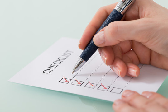 Woman Marking On Checklist Form With Red Pen