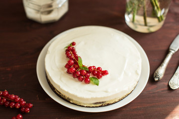 yoghurt cake with currants on wooden background