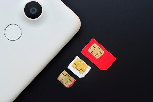 Types of sim cards with smartphone on black background. Mini sim, micro sim and nano sim.