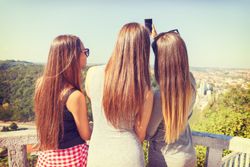 Three girls from behind taking selfie outdoors
