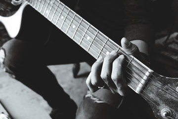 hand of man playing old classic guitar,  vintage dark tones.