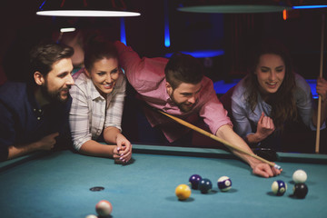 Group of friends playing pool game