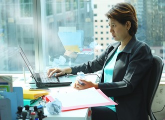 business woman looking at laptop with serious face