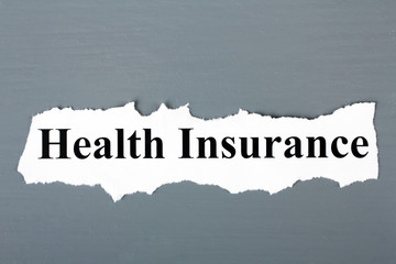 "a piece of paper with the words ""Health Insurance"" on a gray wooden background"