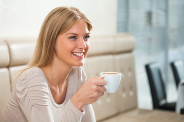 Young happy woman drinking coffee in a cafe