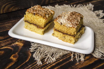 Two slices of sponge cake with nuts and sesame seeds
