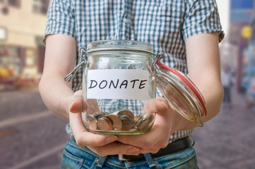Man standing on street is collecting donations in jar.