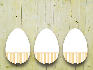 Close-up of three hanged blank Easter egg frames with clips against yellow wooden boards background