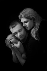 happy family , young parents holding a newborn baby in her arms and gently hugged him, black and white photo on a black background .