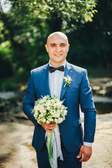 The groom in blue suit with butterfly and bouquet