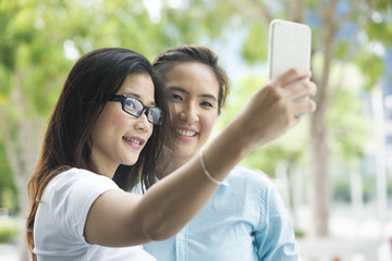 Two happy Asian friends taking Selfie photo in the city.