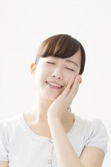 女性 若い 白バック 感情汎用 嬉しい 照れる 気持ちいい 手を頬に 目を閉じる 白バック