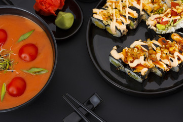 Japanese cuisine. Vegetarian soup with tomato and coconut and crunch sushi roll over black background