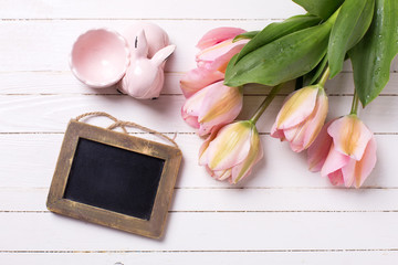 Spring  pink  tulips, decorative rabbit  and empty  blackboard o