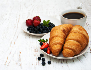 Fresh berries, coffee and croissant
