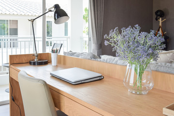 wooden table with computer notebook,pencil,lamp and artificial flowers in modern working area at home
