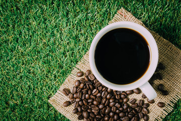 Coffee cup and roasted coffee beans on grass.