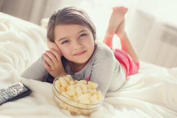 Little girl eating popcorn in bed