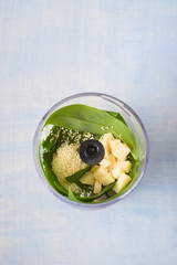Food processor bowl with ingredients for pesto sauce: wild garlic, sesame seeds, olive oil and parmesan cheese