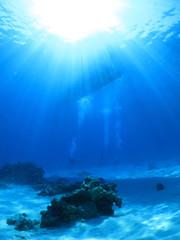 海中から見上げた太陽光の中のボート 沖縄県 阿嘉島